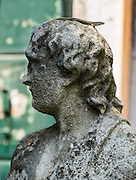 A lizard perches on the head of an old statue, on Torcello island in the Venice Lagoon, Italy, Europe. On Torcello, the Church of Santa Fosca dates from the 1000s AD (as does the adjacent Cathedral of Santa Maria Assunta). Italy's Veneto region is named for the ancient Veneti people from the 900s BC. More than 100 small islands spread across the marshy Venetian Lagoon along the Adriatic Sea in northeast Italy, between the mouths of the Po and Piave Rivers. Barbarian invasions, such as Huns in 452 AD, drove mainland Veniti people to settle the islands. The population of Torcello peaked in the 900s AD with more people than the city of Venice. The Republic of Venice was a major maritime power during the Middle Ages and Renaissance, a staging area for the Crusades, and a major center of art and commerce (silk, grain and spice trade) from the 1200s to 1600s. The wealthy legacy of Venice stands today in a rich architecture combining Gothic, Byzantine, and Arab styles.