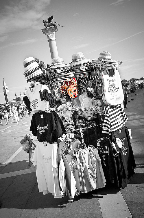 Black and white image of Souvenir kiosk selling venetian masks in Venice Italy with a splash of color.