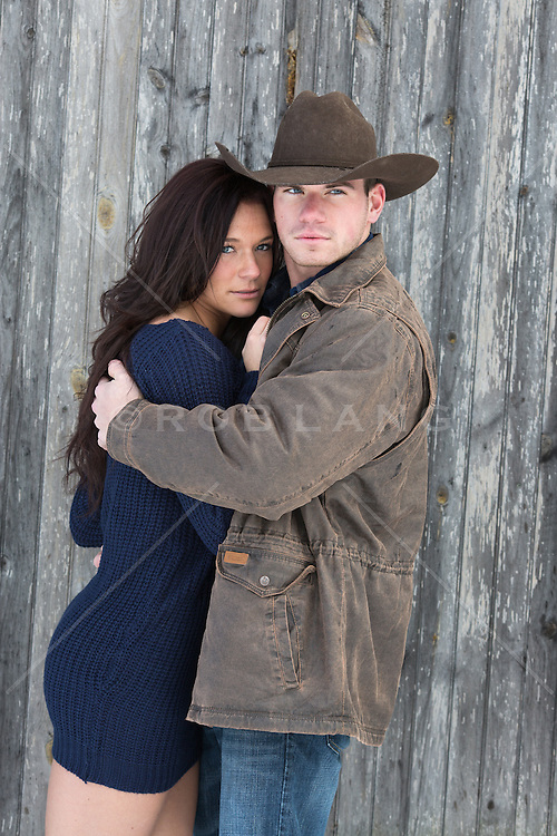 cowboy holding a beautiful woman in a barn