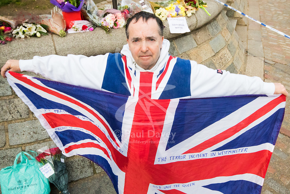 Westminster, London, March 23rd 2017. With his flag and a bunch of Roses John Loughrey of Streatham mourns those killed and injured in Tuesday's terrorist attack on Westminster Bridge and in the grounds of Parliament, in which three people and their attacker were killed with over 40 injured.
