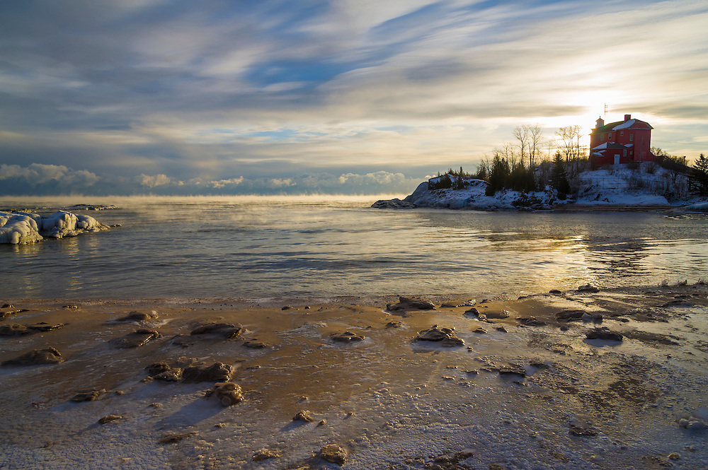Marquette Michigan lighthouse in winter at dawn on Lake Superior.