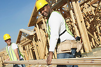 Construction workers carrying boards at construction Site