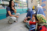 "Pilot, Danielle Aitchison, stops to give money to women and children outside a grocery story in Kabul.  She said, ""You come out and you feel sorry for them.  They have to reduce themselves to being on the street with their children.  You know that probably their husbands have been killed, so it does tug on your heart.""   ..Danielle flies in Afghanistan for The United Nations Humanitarian Air Service (UNHAS).   ..."