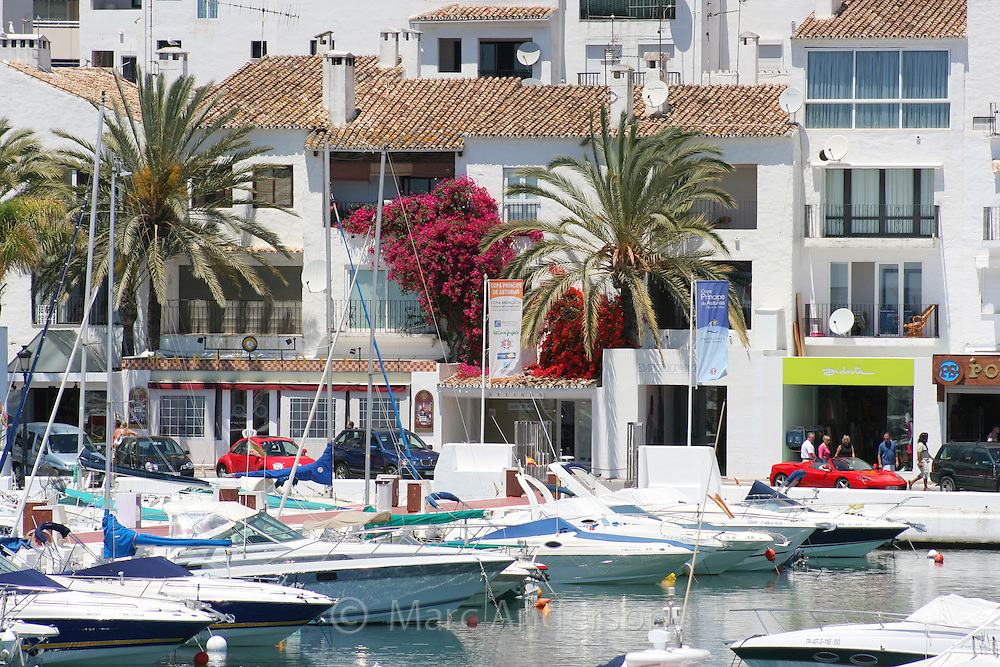 Boats in Puerto Banus harbour, with a red Ferrari in Background, Marbella, Spain