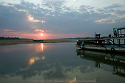 A wooden boat is docked on the Mekong River as the sun sets over Koh Paen Island, Kompong Cham, Cambodia.