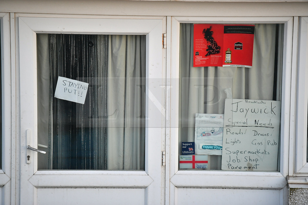 """© Licensed to London News Pictures. 13/01/2017. Jaywick, UK. A sign in the window of a property which reads, """"STAYING PUT"""",  on the seafront at Jaywick before Homes are evacuated in Jaywick, Essex  due to the threat of flooding in low-lying areas . Photo credit: Ben Cawthra/LNP"""