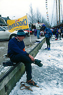 Nederland, Stavoren, 19970104..De Elfstedentocht in januari 1997 in Friesland..Schaatsers rijden door de polders.  Mensen staan te kijken naar de schaatsers die voorbij komen. 6000 schaatsers en meer dan een miljoen toeschouwers..Man trekt zijn houten schaatsen aan...The Elfstedentocht is a speed skating competition and leisure skating tour in the province of Friesland in the Netherlands..6.000 skaters and over a million spectators were present. The route takes the skaters through eleven cities in Frisia, in the North of Holland. 200 kilometre race along the frozen canals of Friesland..Man fastens his wooden skates.