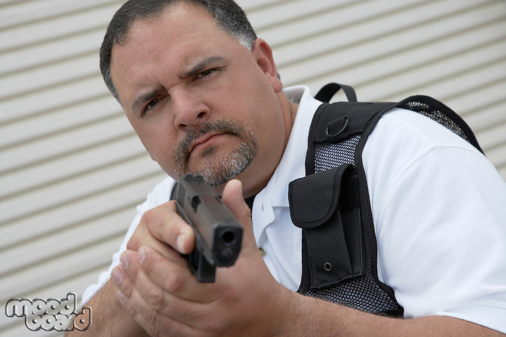 Portrait of security guard in bulletproof vest holding gun