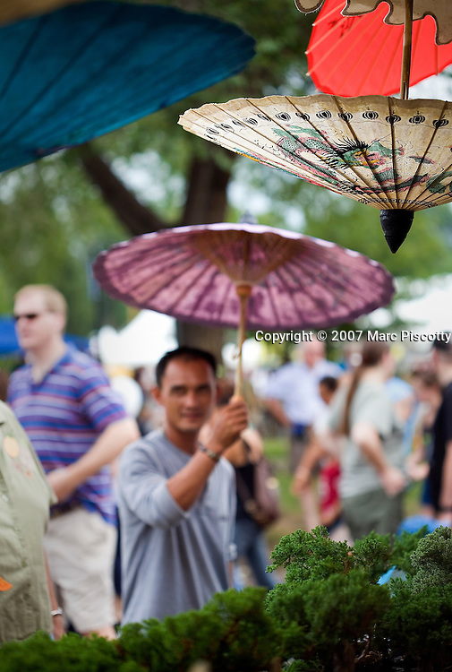 SHOT 7/28/2007 - Vendor Tung Nguyen of Lakewood, Co. tries to entice passersby into buying an umbrella at the Truong An Gifts tent at the 2007 Colorado Dragon Boat Festival. The sport of Dragon boat racing is over 2000 years old and features teams of 18 paddlers - nine men and nine women plus someone to steer the boat all rowing to the beat of a drum and racing to a flag 200 meters away on Sloan's Lake in Denver, Co. Founded in 2001 to celebrate Denver?s rich Asian Pacific American culture, the Colorado Dragon Boat Festival has become the region?s fastest growing and most acclaimed new festival. Festival-goers get to explore the Asian culture through demonstrations, crafts, shopping, eating, and the growing sport of dragon boat racing. .(Photo by Marc Piscotty / © 2007)