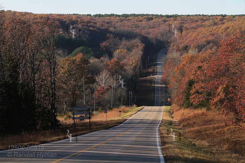 Rural highway cuts through hilly Ozark woodlands in autumn Viburnum, Missouri.