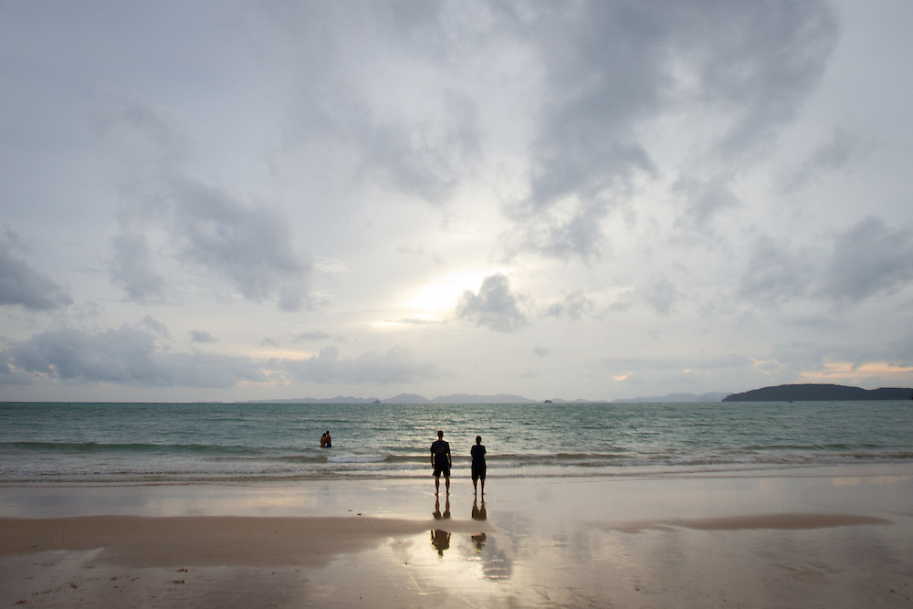 Two couples absorb the sunset on Railay Beach, Thailand.