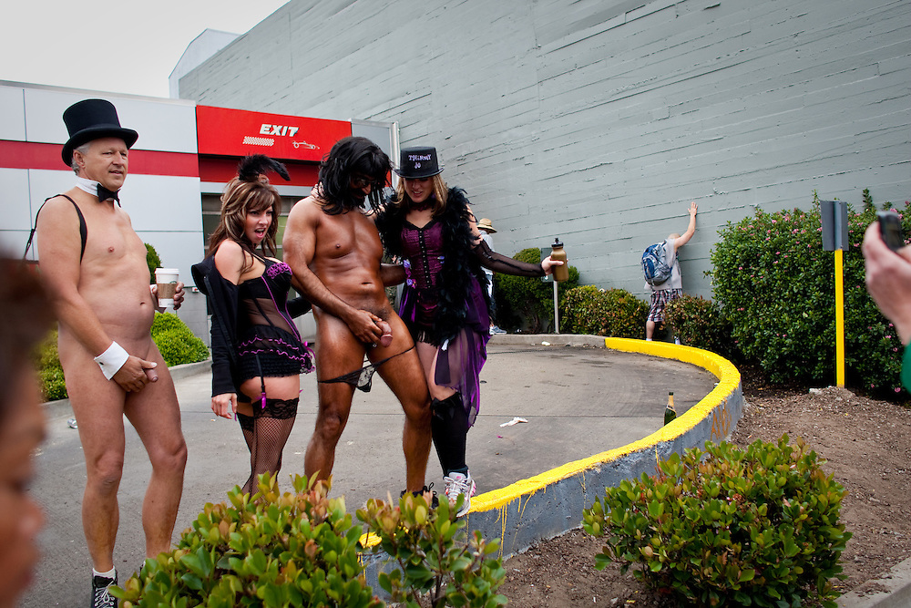 Nudists pose for a photo with other race participants while others urinate near an exit of a car wash