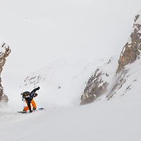 Ian riding his splitboard down a couloir near Rae Glacier