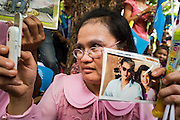 01 AUGUST 2013 - BANGKOK, THAILAND: A woman with up a picture of Bhumibol Adulyadej, the King of Thailand, and his wife, Queen Sirikit, while she uses her smart phone to videotape the crowd in front of Siriraj Hospital, before the King left the hospital Thursday. The King, 85, was discharged from Bangkok's Siriraj Hospital, where he has lived since September 2009. He traveled to his residence in the seaside town of Hua Hin, about two hours drive south of Bangkok, with his wife, 80-year-old Queen Sirikit, who has also been treated in the hospital for a year.   PHOTO BY JACK KURTZ