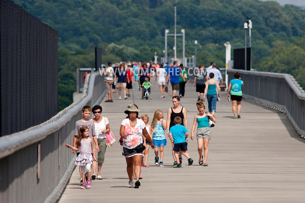 Highland, New York -  People walk across the Walkway over the Hudson on the sunny summer afternoon of June 30, 2014. Walkway Over the Hudson State Historic Park is a linear walkway spanning the Hudson River. At 212 feet tall and 1.28 miles long, it is the longest, elevated pedestrian bridge in the world. The walkway was formerly an abandoned railroad bridge.