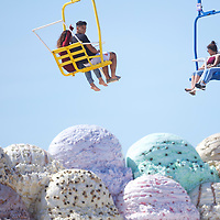 SEASIDE HEIGHTS, NJ - May 21, 2017:  Beach goers ride above a giant sculpture of ice cream on the roof of a boardwalk restaurant in Seaside Heights, NJ May 21, 2017. CREDIT:  Mark Makela for The New York Times