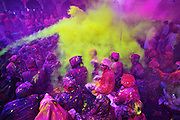 People covered with a layer of Purple colored powder gets sprayed with another layer of yellow while celebrating Braj Holi at Barsana village of Mathura.