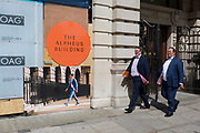 Two businessmen walk past the Alpheus Building on Blomfield Street, a property being refurbished near Liverpool Street Station in the City of London, the capital's financial district - aka the Square Mile, on 8th August, in London, England. The address at 31–35 Blomfield Street is a modern retail space behind a historic Edwardian facade.