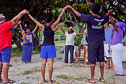 "Sunrise yoga practitioners shout ""Harambe!"" seven times and hold hands in a circle to conclude the morning Kwanzaa celebration.  Harambe means ""Let's all pull together""."