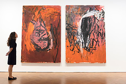 """© Licensed to London News Pictures. 02/10/2018. LONDON, UK. A staff member views """"Rote Elke - Die Flasche (11. Gruppe) (Red Elke - The Bottle (11th Group))"""", 1978, by Georg Baselitz.  Preview of """"A Focus on the 1980s"""", an exhibition of works by Georg Baselitz at Galerie Thaddaeus Ropac in Mayfair.  The show features seminal paintings, previously unseen works, drawings and early sculptures by the artist during his breakthrough decade and runs 3 October to 21 November 2018.  Photo credit: Stephen Chung/LNP"""