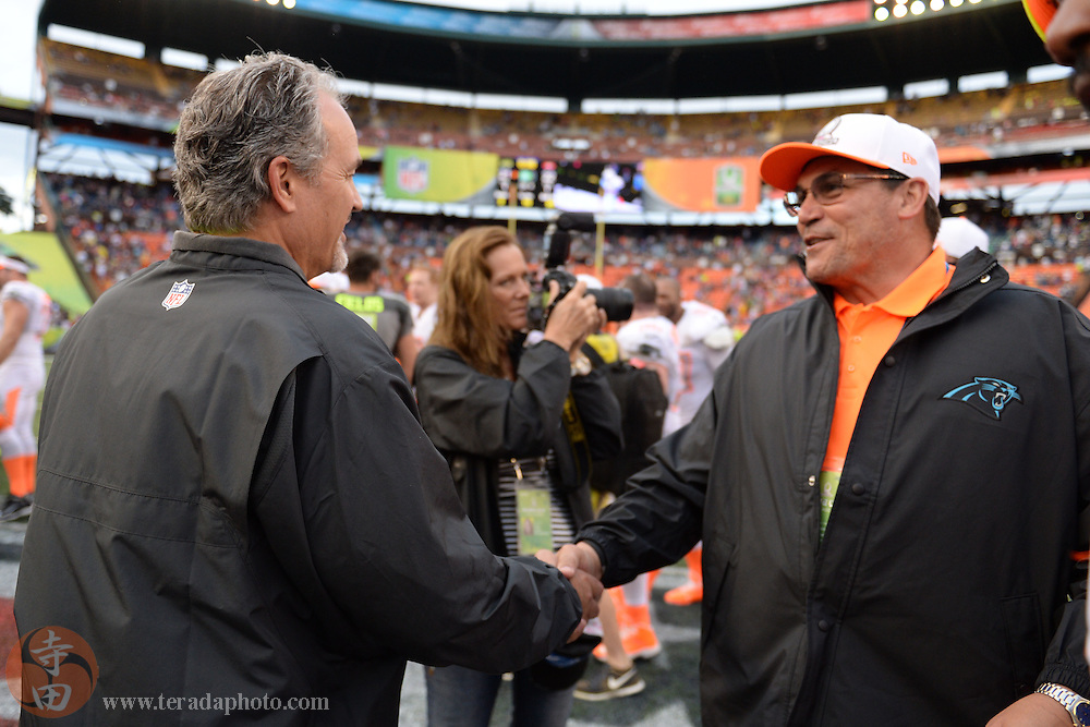 January 26, 2014; Honolulu, HI, USA; Team Sanders head coach Chuck Pagano of the Indianapolis Colts (left) congratulates Team Rice head coach Ron Rivera of the Carolina Panthers (right) after the 2014 Pro Bowl at Aloha Stadium. Team Rice defeated Team Sanders 22-21.