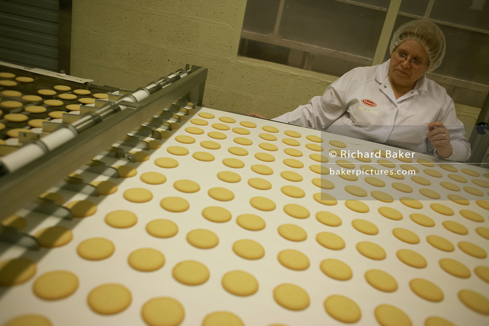 Quality control worker sorts through sub-standard Moments biscuits at the Delacre biscuit production factory in Lambermont