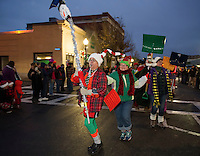 Larry Frates leads the Snow Shovel Brigade down Main Street during the annual Holiday Parade on Saturday evening.  (Karen Bobotas/for the Laconia Daily Sun)