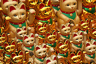 "The Maneki Neko literally ""Beckoning Cat"" is also known as Welcoming Cat, Lucky Cat, Money cat or Fortune Cat.  They are common Japanese decorations, made of porcelain or ceramic,  which is believed to bring good luck to the owner. The sculpture depicts a cat usually  a Japanese Bobtail beckoning with an upright paw, and is usually displayed at the entrance of shops, restaurants  and other businesses. Some of the sculptures are electric and have a slow moving paw beckoning. In the design of the sculptures, a raised right paw supposedly attracts money, while a raised left paw attracts customers."