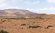 A Berber nomadic shepherd takes a break to make tea while herding goats amid arid terrain near Aoulouz, Taliouine & Taroudant Province, Souss Massa Draa region of Southern Morocco, 2016-05-21. <br />