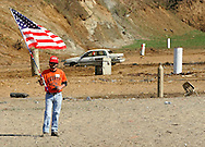 A worker standing on the target range holds the American flag during the playing of the U.S. national anthem during the Knob Creek Machine Gun Shoot near West Point, Kentucky April 10, 2005. Thousands of machine gun and military hardware enthusiasts attended the event held each year over weekends in the spring and fall.