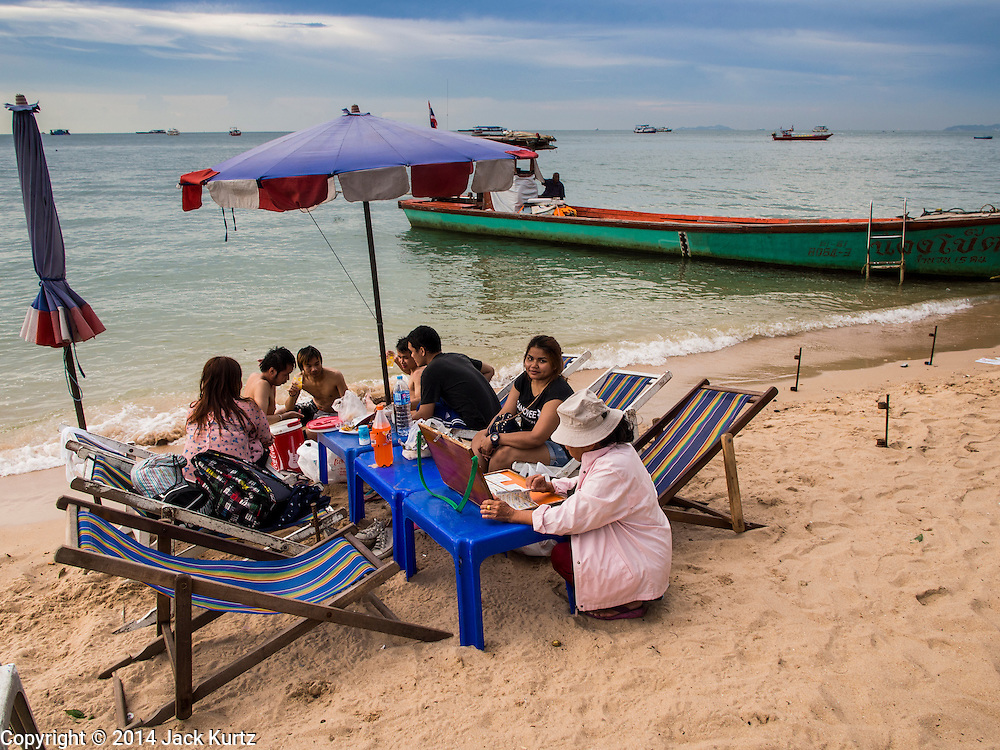 "26 SEPTEMBER 2014 - PATTAYA, CHONBURI, THAILAND: A vendor sells lottery tickets to Thais relaxing on Pattaya Beach. Pataya, a beach resort about two hours from Bangkok, has wrestled with a reputation of having a high crime rate and being a haven for sex tourism. After the coup in May, the military government cracked down on other Thai beach resorts, notably Phuket and Hua Hin, putting military officers in charge of law enforcement and cleaning up unlicensed businesses that encroached on beaches. Pattaya city officials have launched their own crackdown and clean up in order to prevent a military crackdown. City officials have vowed to remake Pattaya as a ""family friendly"" destination. City police and tourist police now patrol ""Walking Street,"" Pattaya's notorious red light district, and officials are cracking down on unlicensed businesses on the beach.     PHOTO BY JACK KURTZ"