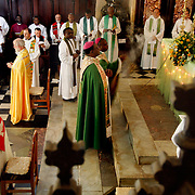 Anglican Archbishop Rowan Williams of Canterbury (left, yellow robe) prays during services at the Anglican cathedral in Zanzibar. Leaders of the world's 77 million Anglicans, in Tanzania for a closed, six-day conference, traveled by boat from the mainland for a Solemn Eucharist in the only Anglican cathedral on this predominantly Muslim archipelago on the Indian Ocean. .