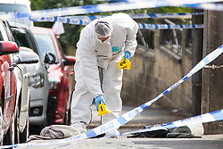 © Licensed to London News Pictures. 16/06/2016. Leeds, UK. Police forensic officer lays markers next to a woman's handbag & shoes at the scene where Police are at the scene in Birstall, south of Leeds, where Jo Cox, Member of Parliament for Batley and Spen, has been shot and stabbed during a constituency surgery. Photo credit: Andrew McCaren/LNP