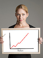 Portrait of young businesswoman showing sales graph against gray background