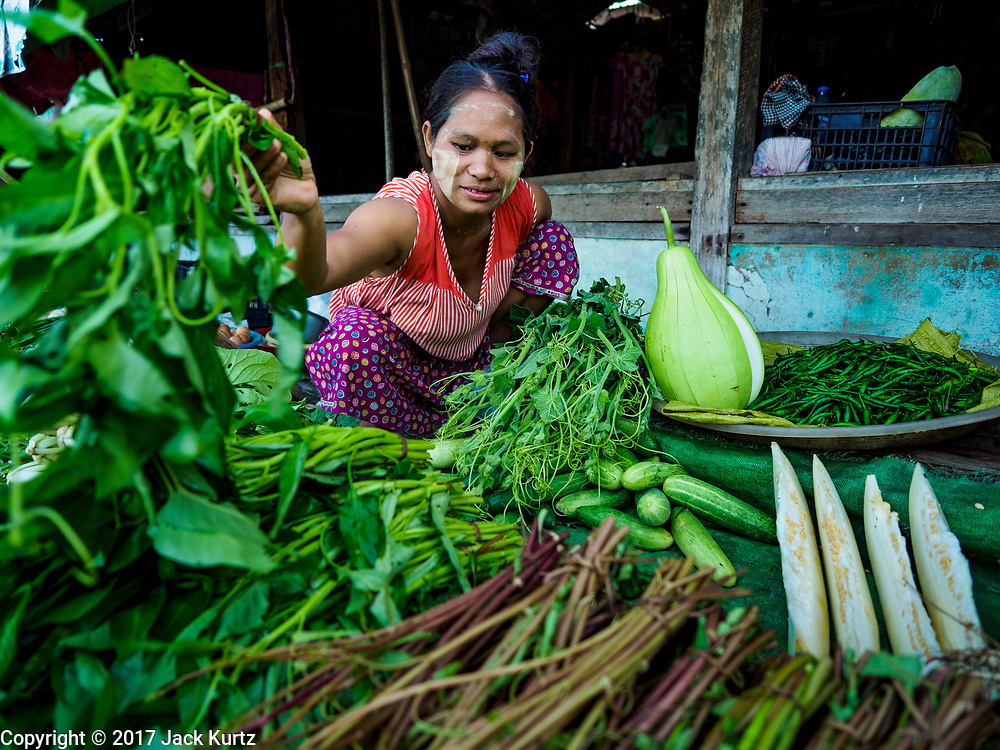 21 NOVEMBER 2017 - PANTANAW, AYEYARWADY REGION, MYANMAR: A vender sets out produce in the market in Pantanaw, a town near Pathien in the Ayeyarwady delta.    PHOTO BY JACK KURTZ