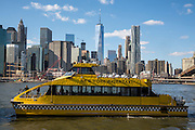 A yellow New York Water Taxi boat sails along the East River, just passing under the Brooklyn Bridge, with Lower Manhattan on the other side of the river.  Photographed across the East River from Brooklyn, New York City, New York, United States of America. <br /> .(photo by Andrew Aitchison / In pictures via Getty Images)