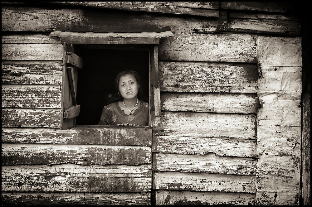 In a remote, impoverished agricultural village in India, a woman gazes out from a window in her home,