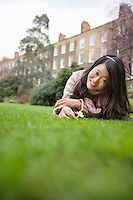 Portrait of a young woman with flower lying lawn in front of building