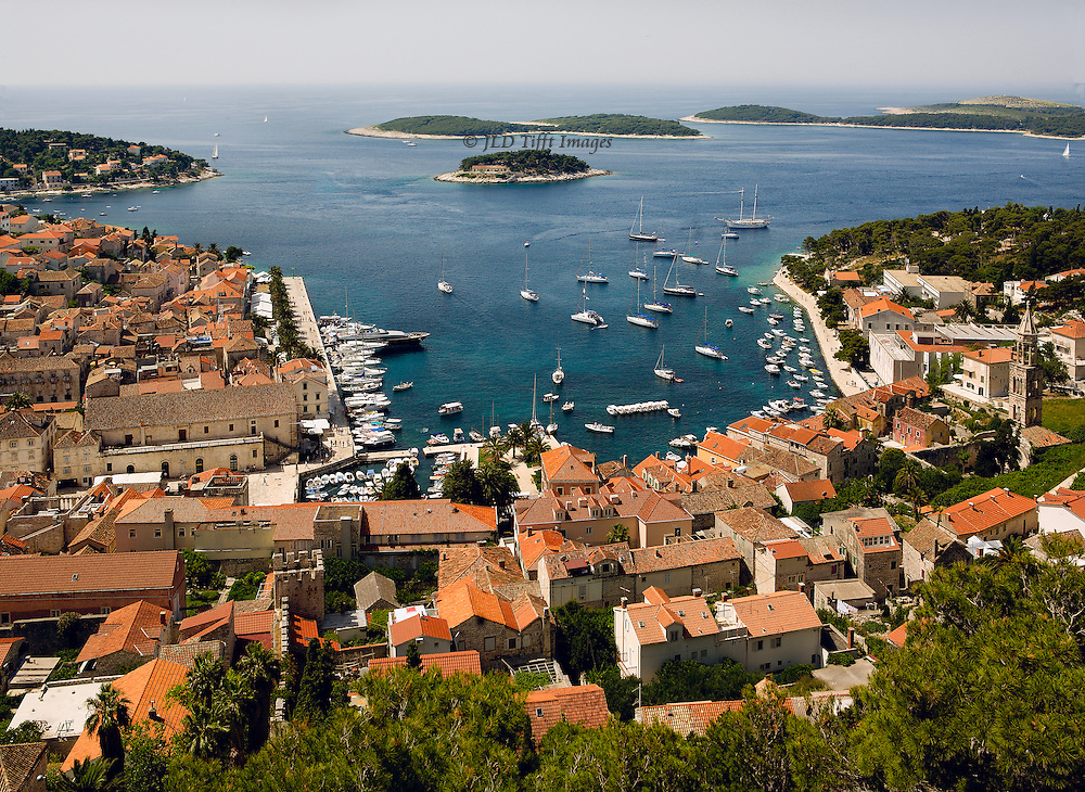Looking down from the fortress on the hill over looking the town showing red tile rooftops cascading down the hill, symmetrical harbor dotted with sailboats, and the scattering of islands in the Adriatic just beyond Hvar.