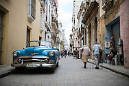 Two elderly people walk past an old American car in Habana Vieja, the historic heart of Havana, Cuba