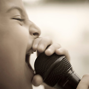 a young girl holding a microphone next to her mouth and singing