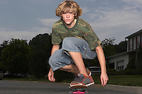 Teenage boy (16-17) skateboarding on street portrait