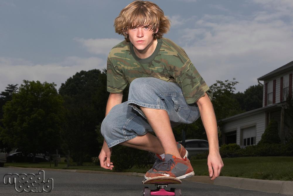 Teenage boy (16-17) skateboarding on street portrait