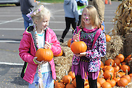 From left, Anya Duffy, 9 and Angelica Frolenko, 10 carry pumpkins they had just chosen at the annual fall festival Saturday October 24, 2015 in Bristol Township, Pennsylvania. (Photo by William Thomas Cain)