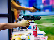 24 NOVEMBER 2018 - BANGKOK, THAILAND:  A child learns how to handle a handgun at the Royal Thai Police Academy booth at the Red Cross Fair in Bangkok. The Red Cross Fair is a fund raiser and an annual event that draws thousands of attendees every night of its nine day run. This is the first year the fair has been in Lumpini Park. Previously it had been held in the Dusit section of Bangkok. The 2018 Fair marks 125 years of service for the Red Cross in Thailand.    PHOTO BY JACK KURTZ