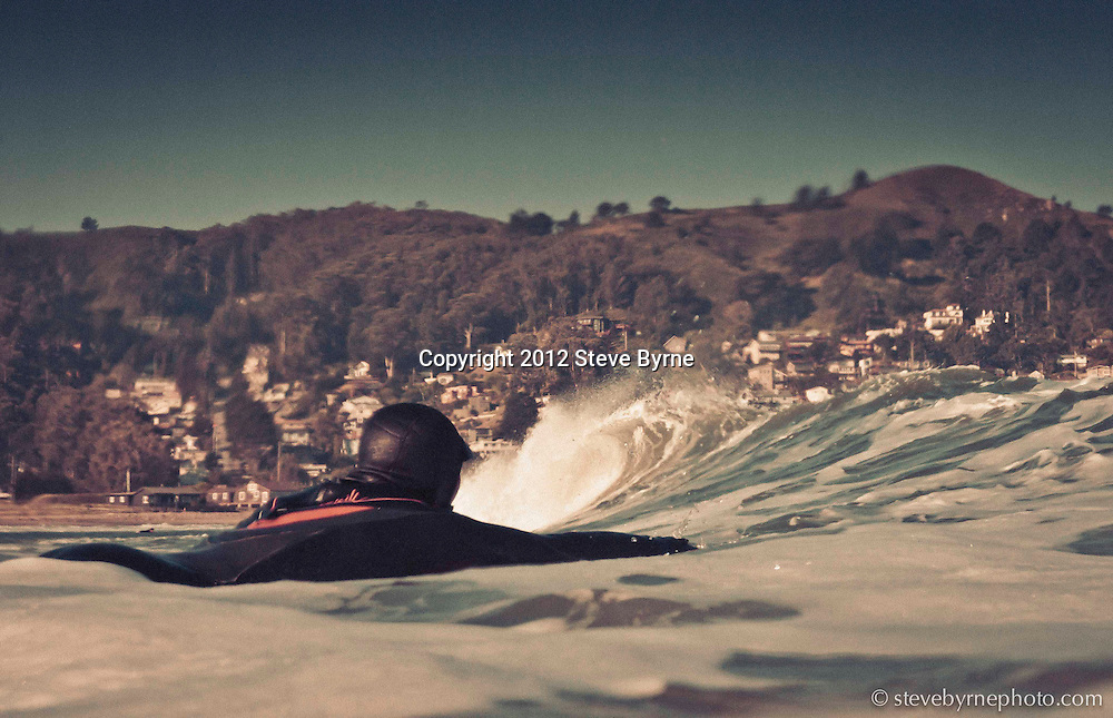 A surfer paddles out for a morning session at Lindamar Beach, Pacifica, California.