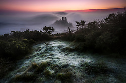 © Licensed to London News Pictures. 21/01/2020. Corfe Castle, UK. Corfe Castle in Dorset shrouded in mist behind a frost covered hillside, as large parts of the UK are hit by freezing temperatures. Photo credit: Peter Scott/LNP