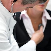 Nederland Rotterdam  25-08-2009 20090825 Foto: David Rozing .Serie over zorgsector, Ikazia Ziekenhuis Rotterdam. , Arts met stethoscoop luistert naar de hartslag  van een vrouw. Doctor stethoscope, listening to heart of woman / patient, heart rate.  - in scene gezet - ..Foto: David Rozing ..Holland, The Netherlands, dutch, Pays Bas, Europe, routine
