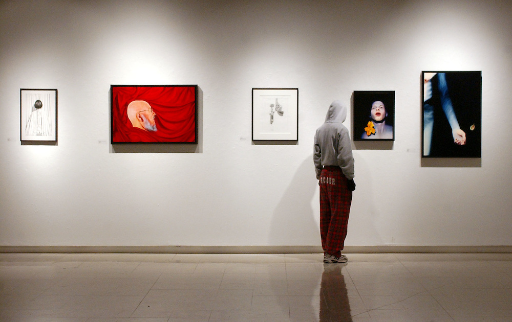 16684Faculty Art Exhibit at Seigfred Hall: Photos by Colby Ware..10/18/04--A visitor admires paintings by John Sabraw.