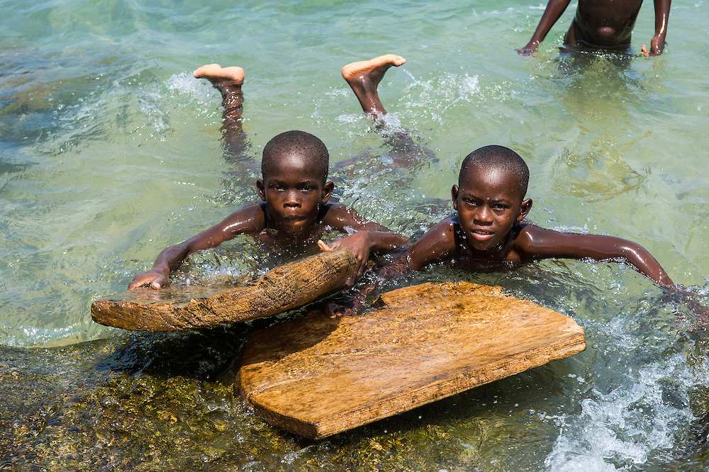Young children having fun in the water with wooden surfboards  in the fishing village Morro Peixe in northern Sao Tome, Sao Tome and Principe, Atlantic ocean